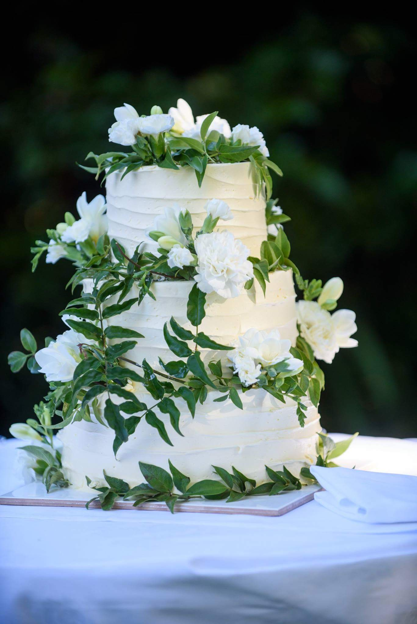 3 tier white wedding cake with flowers and greenery